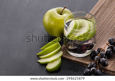 Summer fresh fruit Flavored infused water mix of apple and grape over black background - stock photo