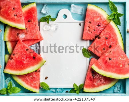 Summer fruit concept. Watermelon slices with ice cubes and mint leaves on blue wooden background, white ceramic board in center. Top view, copy space - stock photo