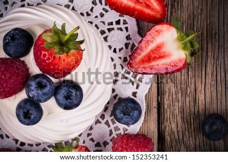 Summer fruit pavlova closeup, over vintage style wood background. - stock photo