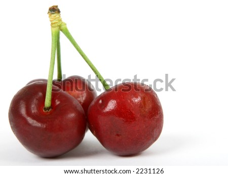 Summer fruit salad ingredients, healthy red cherries on green stalks, macro close up with copy space - stock photo