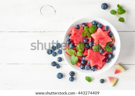 Summer fruit salad of watermelon and blueberries. Slices of watermelon in the shape of a star. Top view, flat lay - stock photo