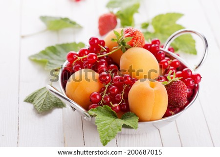 Summer fruits apricots, red currant, strawberry in bowl on white wooden background. - stock photo