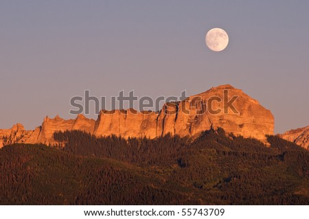 Summer Full Moon rising over Courthouse Rock a prominent feature in the Cimmarron Mountains - stock photo