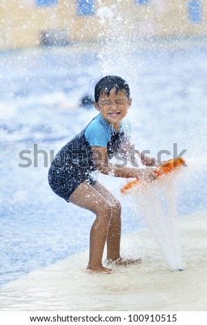 Summer fun at the water park. Boy playing  at swimming pool - stock photo