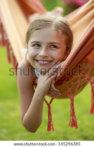 Summer fun in the garden - lovely girl playing in hammock - stock photo