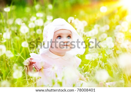 Summer fun, sweet little girl, sitting and blowing dandelion on the meadow