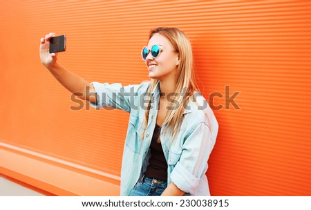 Summer, fun, technology and people concept - cool hipster girl makes self-portrait on the smartphone outdoors against colorful orange wall - stock photo