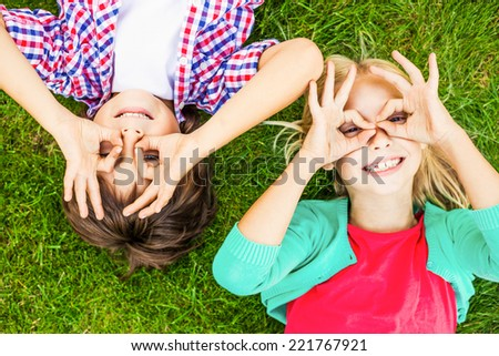 Summer fun. Top view of two cute little children making faces and smiling while lying on the green grass together - stock photo