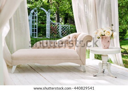 Summer garden gazebo with curtains and sofa for relaxation - stock photo