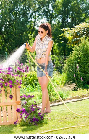 Summer garden smiling woman watering hose flower sunny day - stock photo
