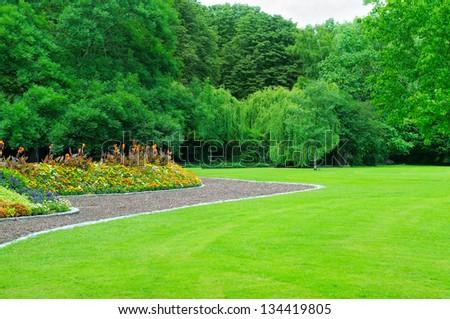 Summer garden with lawn and flower garden - stock photo