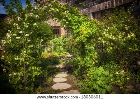 Summer garden with paved path and trellis - stock photo