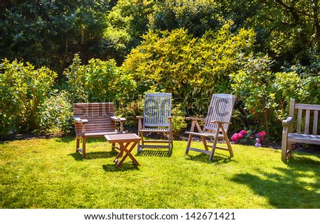 summer garden with wooden furniture - stock photo
