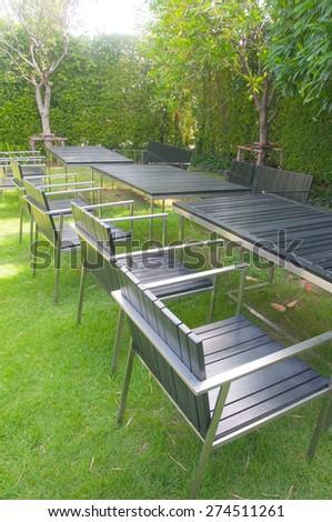 Summer garden with wooden furniture - stock photo
