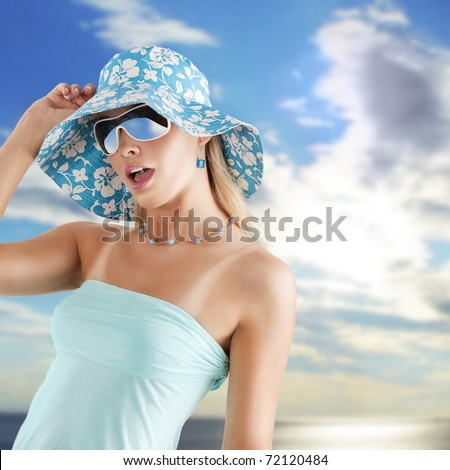 summer girl in light blue with hat and sunglasses in hot expression