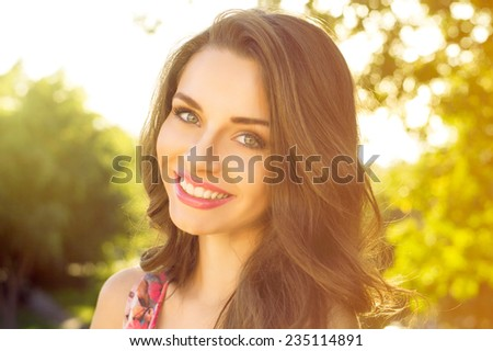 Summer girl portrait. Caucasian woman smiling happy on sunny summer or spring day outside in park - stock photo