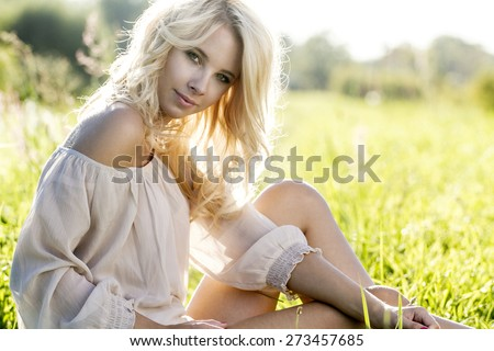 Summer girl portrait. Young attractive Caucasian woman outdoor sitting on the grass.