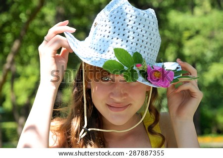 Summer. Girl's portrait in blue hat with rose flower - stock photo