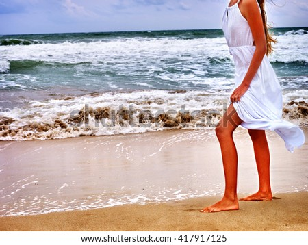 Summer girl sea.  Woman goes at water on coast. Bare feet on sea beach.
