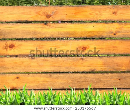 Summer grass and old wooden planks on green background - stock photo