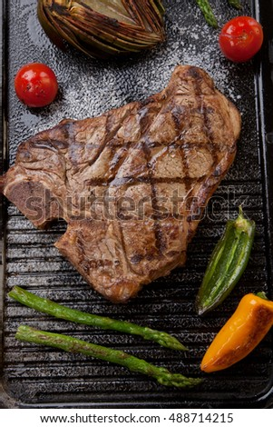 Summer grill - grilled T-bone steak and assorted grilled vegetables - asparagus, mini pepper, and tomatoes - on griddle.