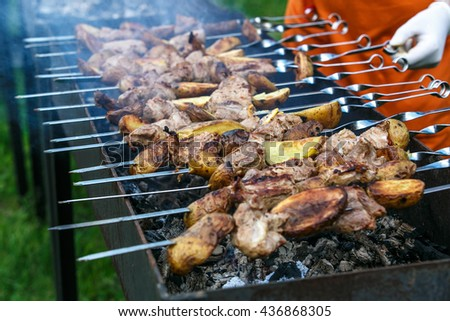 Summer grilling shashlik on barbecue grill. Selective focus - stock photo