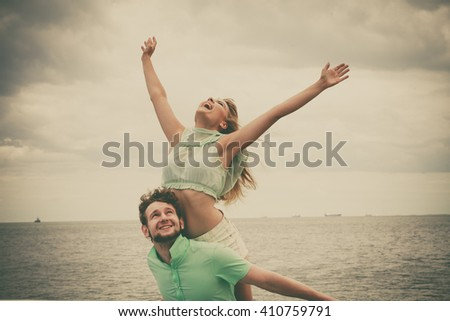 Summer happiness concept. Woman and man young couple in love playing sharing free time having fun outdoor on sea pier sky background