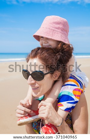 summer happy family of two years old blonde baby with pink hat white shirt and colorful trousers carrying on shoulders or shouldering of woman mother black sunglasses smiling at sand beach - stock photo