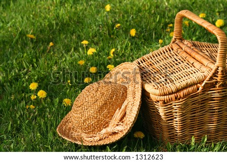 Summer hat and wicker basket on the grass