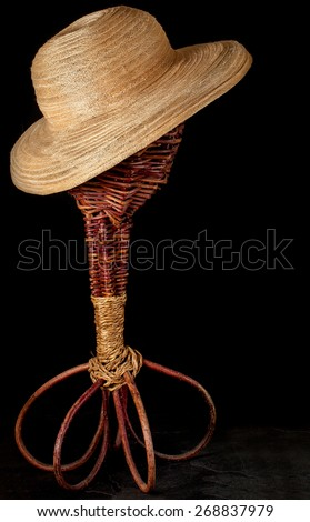Summer hat on a vintage wicker rustic hatstand. Black background with copy space. - stock photo