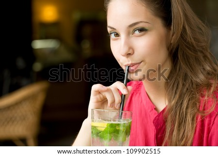 Summer heat refreshment, gorgeous young brunette drinking lemonade.
