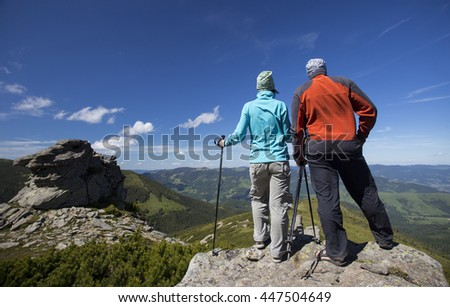 Summer hiking in the mountains with a backpack and tent. - stock photo