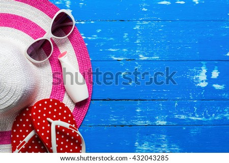 Summer holiday background, Beach accessories on wood table, Vacation and travel items, Red flip flop with sunglasses, moisturizer and summer beach hat on wood table - stock photo
