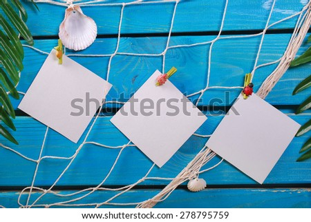 summer holiday background with blank cards pinned to the fishing net hanging on blue wooden planks - stock photo