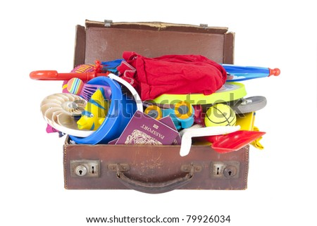 summer holiday beach and vacation suitcase packed full of clothes and toys - stock photo