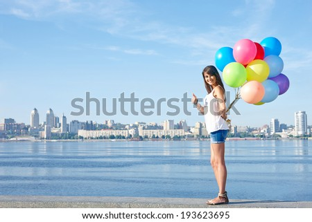 Summer holiday, celebration and present concept: happy young woman holding colorful balloons behind back and gesturing thumb up, standing in full length, city view, outdoors - stock photo