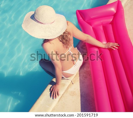 Summer holiday fashion concept - tanning woman at the swimming pool