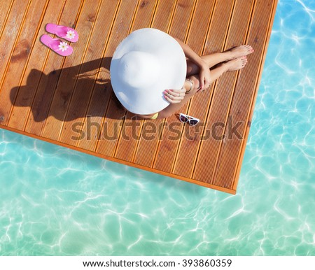 Summer holiday fashion concept - tanning woman wearing sun hat at the pool on a wooden pier shot from above - stock photo