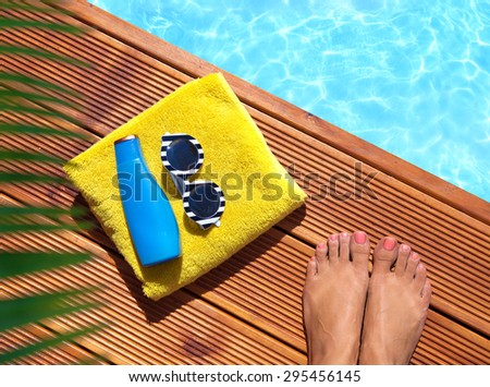 Summer holiday fashion concept -  woman  on a wooden pier at the pool - stock photo