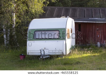 Summer Holiday in Finland. An old retro caravan sits in the field of a camping ground, basking in the midnight sun of far north west Finland. Surrounded by long grass, the caravan looks rustic.
