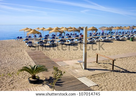 Summer holiday scenery, sandy beach by the blue sea, deckchairs, wooden path and a shower in Marbella resort on Costa del Sol in Spain. - stock photo