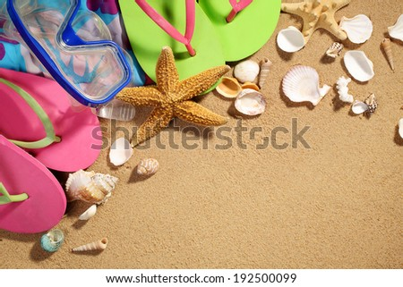 Summer holiday setting with flip flops,diving goggles and seastars on beach - stock photo