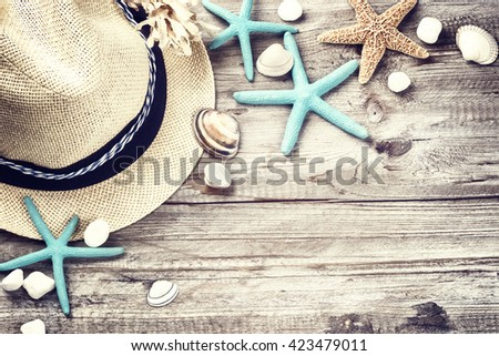 Summer holiday setting with straw hat and seashells on wooden background - stock photo
