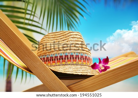 Summer holiday setting with straw hat on beach chair  - stock photo