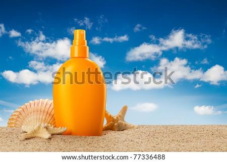 Summer holiday - suntan oil on beach - stock photo