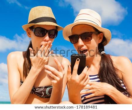 Summer holiday, technology and beach concept. Girls using smart phone on the beach. Gossip girls. - stock photo
