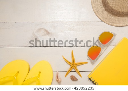 Summer, Holiday, Travel. Summer beach decoration:  yellow items of sunglasses, straw hat, flip-flop and starfishes on mint wooden background - stock photo