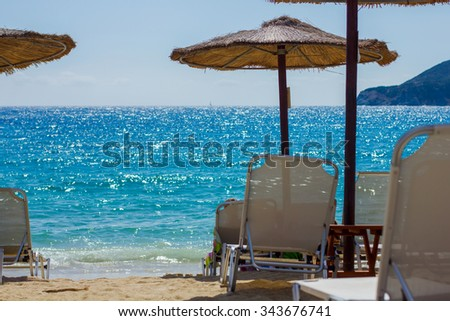 Summer ,Holiday, Travel, Vacation concept ,Sunshade and Chairs on the Sandy Tropical Beach over blue summer sky. - stock photo