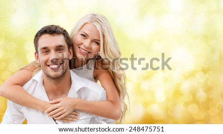 summer holiday, vacation, dating and love concept - happy couple having fun over yellow lights background - stock photo