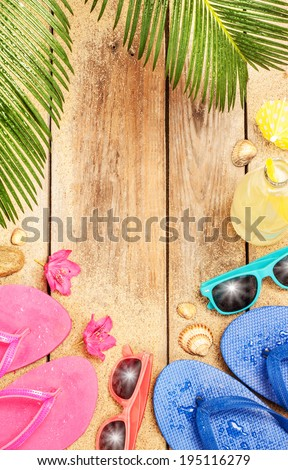 Summer holiday (vacation) tropical beach background layout with free text space. Palm tree leaves, sand, exotic flowers, sunglasses and flip flops on vintage wood - poster design. - stock photo